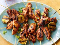 Grilled Yucatan Chicken Skewers from Bobby Flay 6 chicken thighs, skinless and boneless, cut in half lengthwise 1/2 cup fresh squeezed orange juice 1/4 cup fresh squeezed lime juice 2 tablespoons canola oil 2 tablespoons ancho chile powder 3 cloves garlic, coarsely chopped 2 tablespoons chipotle in adobo sauce, pureed Salt and freshly ground black pepper Chopped scallions, for garnish Grilled lime halves, for garnish