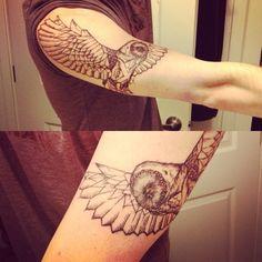 geometric owl tattoo on upper arm
