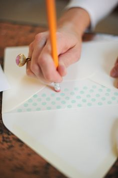 I love how simple and up close this photograph is. Makes me feel like I'm there with her, watching her stamp those polka dots onto the envelope. This would definitely entice readers who are creative... Love the angle as well, like looking at it from a friend-in-the-room's point of view