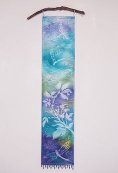 "Purple Turquoise Green Dragonfly Wall Art Tapestry. Misty nature silhouettes float over vibrant, watercolor hues in this unique hanging Art Panel. It is hand painted using a textile pigment on silky fabric, resulting in a subtle texture and shimmer. It measures 8"" x 36"", a long narrow painting perfect for small spaces. Delicate loops of ribbon allow it to be hung on a decorative rod or branch, while beaded fringe at the bottom adds a bit of sparkle and weight for a nice drape. Each Art…"