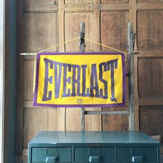 VINTAGE EVERLAST BANNER, ORIGINAL 1930s EVERLAST BOXING FELT BANNER, SPORTS DECOR, SPORTS NURSERY, CROSSFIT, BOXING BANNER, MMA  Stunning piece of athletic history! Displays great. Original, circa 1930s, EVERLAST advertising banner. EVERLAST started in 1910 making quality swimwear. By the early 1920s it was a premier sports brand, with a focus on boxing gear. All felt construction, purple applique lettering on gold-yellow background, stitched purple border. Original dowel and string for…