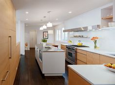 modern kitchen, dark wood floors, light cabinets, white island and counter tops. Needs more pops of color.