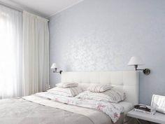 ห้องนอนหลักใช้โทนขาวเทา ม่านกรองแสงสีขาวและวอลล์เปเปอร์ลายดอกไม้ช่วยให้ห้องดูอ่อนหวานขึ้น
