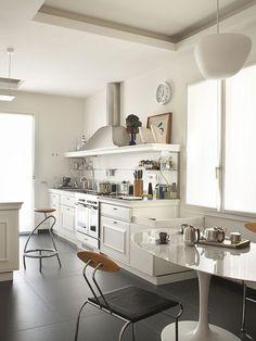 piso preto em cozinha branca com mesa saarinen