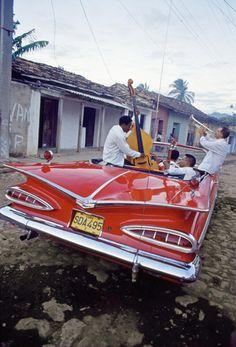Músicos en un viejo Chevrolet Impala de 1959 por una calle de Trinidad, en Cuba. / Álvaro Leiva, El País