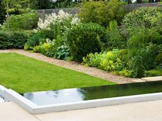 A beautifully landscaped yard with a gravel border is paired with a chic infinity pool. Shades of green plants round out the layered landscape.