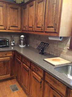 Rustic basswood kitchen cabinets with antique brass modern hardware. 1990s cabinet update.  Corian countertops.
