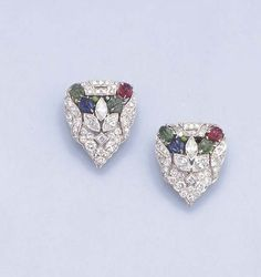 A PAIR OF ART DECO DIAMOND AND GEM-SET CLIP BROOCHES  Each of triangular outline, the central palmette of marquise-cut diamonds to the carved emeralds, ruby and sapphire, with circular-cut diamond border, circa 1925, 2.4 cm. high