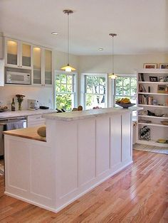 Dual level island with Marble and Butcher Block in a white kitchen with pendant lights.