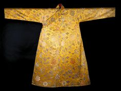 Man's yellow Chinese silk robe woven with a design of peony scroll in coloured silks, and silver metal strip brocading, with glazed cotton lining of English manufacture: Tibetan, 19th century  Museum reference A.1983.1007