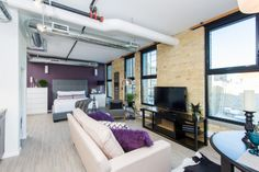 The WATERFRONT at District Condos - Loft style conversion condos featuring exposed brick, century old wood beams, and modern finishes. Perfect bachelorette/bachelor pad - also has enclosed den/ room/ office space near front.