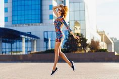 fashion  happy positive summer portrait of cute sexy woman in bright mini dress jumping on the street sunny