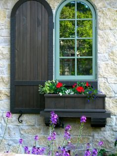 a window box, and a beautiful unique shutter make a statement in this wall