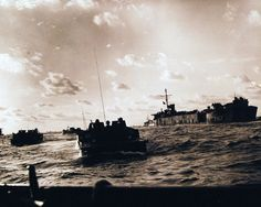80-G-304871: Battle for Iwo Jima, February-March 1945. Off the fire-swept beaches of Iwo Jima, Amtracks loaded with Marines emerge from the depths of a Coast-Guard manned LST-787 at the right and surge toward shore on D-Day. Photographed February 19, 1945. U.S. Navy Photograph now in the collections of the National Archives.