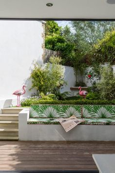 The slice of garden is cleverly designed in receding sections decking seating hedge lawn and a raised bed which creates the illusion of depth as if it fades into the distance. The white concrete retaining wall has been customised into a tropical bench. Garden Retaining Wall, Concrete Retaining Walls, Sloped Garden, Concrete Garden Bench, Concrete Blocks, Patio Steps, Garden Steps, Deck Patio, Patio Roof