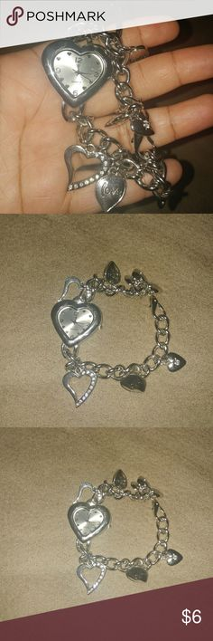 "Heart Charm Watch Bracelet This very cute silvertone watch is NOT brand new, but you wouldn't know that from looking at it. It is shiny and has no tarnish. I've had it for a VERY long time & took good care of it. It has darling heart charms spread out all along it. Some of the heart charms have rhinestones or say words like ""love"" The watch face itself is shaped like a heart. This is a fun piece to pair with some denim or khaki shorts and a cute little tank with your fave pair or sandals…"