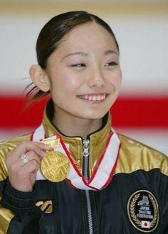 フィギュアスケートの全日本選手権最終日は2003年12月27日、長野市のビッグハットで行われ、女子で16歳の安藤美姫(オリオンク、愛知・中京大中京高校1年生)が女子で大会初の4回転ジャンプに成功し、初優勝を飾った。  前日のショートプログラム(SP)で2位につけた安藤は、この日のフリーで1位となって逆転。先のグランプリ(GP)ファイナルで優勝した村主章枝(新横浜プリンスク)、GPファイナル3位の荒川静香(早大)ら有力選手を抑え、新女王の座に就いた。  写真は、金メダルを見せる女子優勝の安藤美姫 【時事通信社】