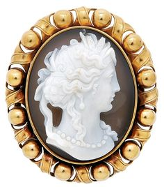 An Antique Hardstone Cameo and Gold Brooch, circa 1890  The 18k gold oval openwork frame designed with a series of boules and crossover ribbon ties, centering an oval hardstone cameo depicting the profile of a classical lady, with fitted box