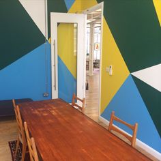 Colourful office wall decoration. Geometric pattern in yellow, green and blue paint.