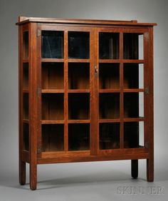 Arts & Crafts Stickley Brothers China Closet  Oak and glass  Michigan, c. 1912  Rectangular top over two doors each with eight panes of glass, four pane side lights raised on four square posts gently tapered at feet, interior fitted with three shelves, branded mark, ht. 59 1/2, wd. 46 1/4, dp. 14 5/8 in.