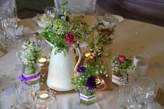 Vintage Jugs, pitchers and glass vessels were filled with posies of fresh flowers