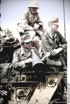 Two German Afrikakorps soldiers rest in their vehicle while an officer attempts to coordinate his unit's movements in North Africa, March/Ap...