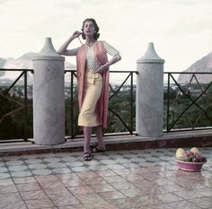 ca. 1955, Palermo, Sicily, Italy -Model standing on terrace wearing sharkskin straight yellow skirt with striped jersey shirt over sleeveless orange overcoat