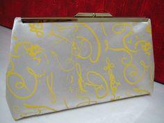 Bolsa Clutch em cetim de seda estampada com grafismos amarelos. Forrada com cetim de seda perola. Costura francesa. Fecho em metal prateado. Opcional alca de corrente, solicitar por email. R$ 50,00