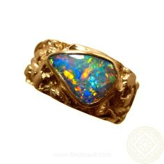 A Boulder Opal ring for men in 14k Gold. The Boulder Opal weighs 2.5 carats and has Red and Blue colors. The 14k Gold ring weighs 17 grams and has a rough texture. #opalsaustralia