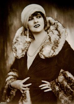 A flapper wearing fur and a turban.