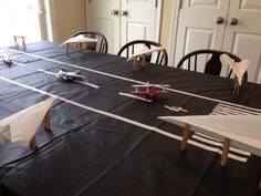 "Airplane birthday party. This is what we wound up doing for the table. White duct tape on black vinyl tablecloth with toy airplanes on the ""runway"". The white airplanes are paper towels for each kid's napkin."