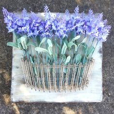 Basket string and nail wall decor with artificial lavender flowers.  This art piece is a solid wood plaque, that can be stained or painted in any color. *This piece includes 15 flowers* Flowers are removable and can be changed to suit the season or decor.  These signs are approximately 12x12 inches (23cm x 23cm) and include the flowers. They come with a hanger on the back so you can open it and hang it right away!  This item is completely customized for you! When ordering, leave a note with…