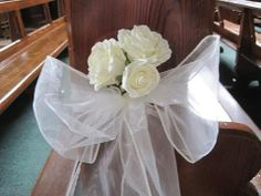 Flowers pinned to chair and use tulle to make bow