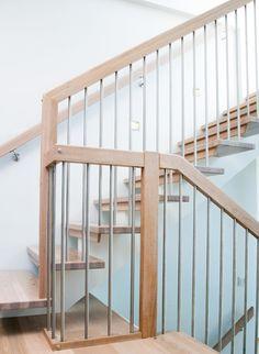 Modell Maia, her vist som 180° tett og åpen trapp, med kombinasjon av underliggende og midtstilt vange. Vanger er malt i farge hvit S 0502Y, spiler i børstet rustfritt stål, resten i hvitbeiset lakkert eik.