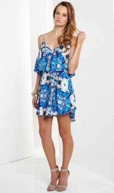 Blossomy Dress by Ministry of Style by BEBE has a low v-shaped neckline with thin adjustable spaghetti straps. The women's dress has a relaxed bodice, with a frill overlay. The waist is elasticized at the mid-waist with a gathered dress skirt .