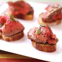 Filet Mignon with Garlic Toasts - 7_INGREDIENTS - 1 spray(s) cooking spray 8 clove(s) (medium) garlic clove(s), peeled (or to taste) 1 Tbsp olive oil 1 tsp fresh lemon juice 3/4 tsp table salt 1/4 tsp black pepper 1 1/2 Tbsp fresh parsley, fresh, finely minced 2 pound(s) uncooked trimmed beef tenderloin, trimmed and tied (from butcher) 24 oz French bread, cut into sixty four 1/3-inch-thck slices