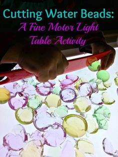 A fun fine motor activity! Cutting water beads on the light table - Where Imagination Grows Cutting Activities, Fine Motor Activities For Kids, Sensory Activities, Sensory Rooms, Sensory Play, Fine Motor Skills Development, Water Beads, Early Learning, Light And Shadow