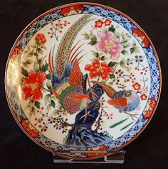 Small attractive Japanese plate featuring two colourful pheasant-like birds surrounded by flowers and a decorative border with floral motifs.
