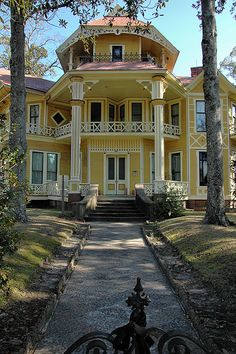 "Though this house is massive, it's very welcoming.  I love the center ""tower"" and the 2nd floor porch.  I also like that it is NOT symmetrical.  The setting with trees and pretty landscaping helps the welcoming feel."