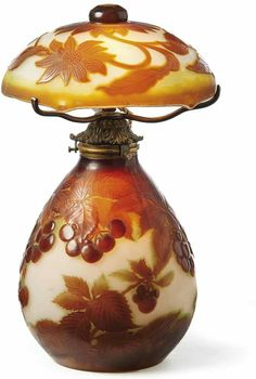 "Lamp Emile Gallé, Nancy - about 1900 u. 1920/25 Stark bulbous feet with cherry branches, the domed shade with floral decoration. Colorless glass with green and red-brown flashed, etched decorative, sometimes acid polished. At the foot bez. ""Gallé"" on the screen with japonisierender signature. H. tot. 43 cm."