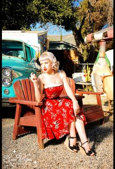Netti Dress by Pinup Couture in bright Red Cowboy Print; pert platinum blonde, red lipstick, black wedge shoes, aqua truck in 'trailer trash' or rockabilly setting.