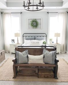 I adore this farmhouse style bedroom with the antique wood bench at the end of the bed and the light bright features of the room.
