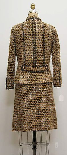 """Suit House of Chanel (French, founded 1913) Designer: Gabrielle """"Coco"""" Chanel (French, Saumur 1883–1971 Paris) Date: ca. 1962 Culture: French Medium: a) wool/mohair/synthetic, silk, plastic, metal; b,c) wool/mohair/synthetic, silk Dimensions: Length at CB (a): 23 1/2 in. (59.7 cm) Total Length (b): 9 in. (22.9 cm) Length at CB (c): 21 3/4 in. (55.2 cm) Credit Line: Bequest of Yolande Fielding–Scheftel, 2006"""