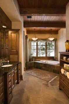 Spacious quarters with beamed ceilings, warm wood cabinetry, dark marble, and a huge soaking tub  ... luxurious. ❤️  #cabin#bathroom#lodge