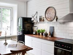 This is what I truly want - a white kitchen with a black Smeg fridge! My absolute favourite.