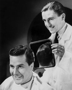wondercut:      Man inspecting the back of his new haircut in a barber's mirror, c 1940s