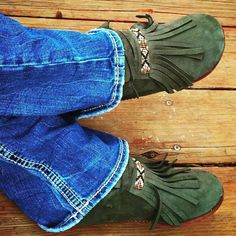 Our Patina Moc is handmade with our supple dark green deerskin leather, accented brown deerskin tong trim, and flexible rawhide soles. These new favorites are simple mocs with intricately hand- beaded geometric designs across the top of the fringe. Hand-crafted and sewn with size 11 seed beads, hand-stitched together with sinew. Combining hues of bronze, topaz, black, golds, white and silver. #PatinaMoc #moccasins #comfort #deerskin #footwear #artisan #bohochic #boho #nativemade #native