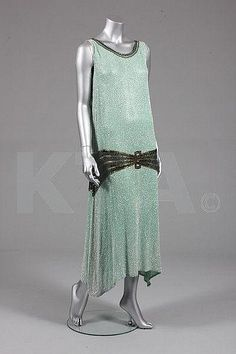 A pale green beaded evening gown, circa 1929. The dress style during the 1920's entailed the elusive hemline to give the illusion of being first long and then shorter with dripping fabrics.