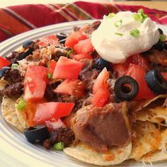Over the Top Nachos | Ground beef is the key to these hearty classic nachos. It's generously spread over the chips before cheese and toppings.