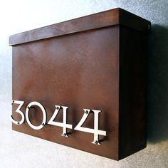 Modern mailbox with floating numbers and a rusted box